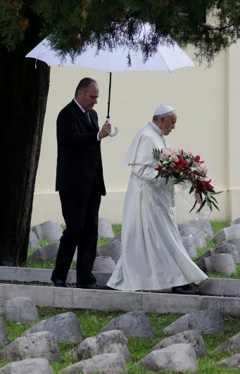 El papa Francisco carga flores durante su visita al cementerio austro-húngaro en Fogliano di Redipuglia, en el norte de Italia, el sábado 13 de septiembre de 2014.   (AP Foto/Luca Bruno)