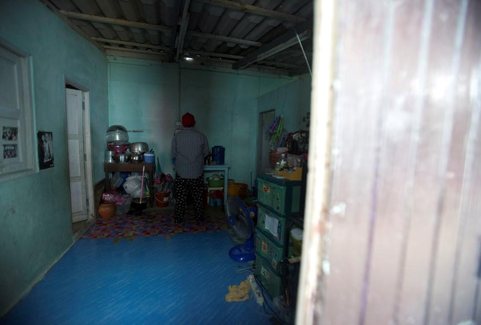 Wassana, una madre por encargo tailandesa que dio a luz uno de los múltiples hijos que tuvo un joven japonés, fotografiada de espaldas en la habitación donde vive en un barrio marginal de Bangkok el 29 de agosto del 2014. Wassana, cuya familia tenía muchas deudas, cobró 10.000 dólares y no hizo demasiadas preguntas. (AP Photo/Sakchai Lalit)