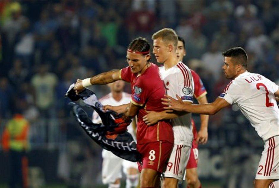 El jugador de Serbia, Nemanja Gudelj, izquierda, agarra una bandera mientras forcejea con el jugador de Albania, Bekim Balaj, centro, durante un partido por las eliminatorias de la Euro el martes, 14 de octubre de 2014, en Belgrado. (AP Photo/Darko Vojinovic).
