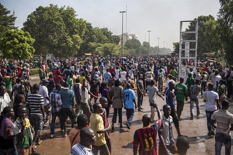 Centenares de manifestantes recorren las calles de Uagadugú, Burkina Faso, donde se desató el caos después de que un numeroso grupo de ellos asaltaran e incendiaron el Parlamento en protesta por la votación de la enmienda constitucional impulsada por el jefe de estado para prolongar su mandato, hoy, jueves 30 de octubre de 2014. EFE/Str
