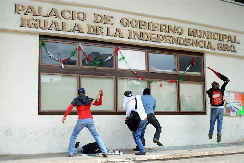 MEX17. IGUALA (MÉXICO), 22/10/2014.- Un grupo de manifestantes causa destrozos el miércoles 22 de octubre de 2014, en el ayuntamiento del municipio mexicano de Iguala, donde lanzaron cócteles molotov contra el edificio en protesta por la desaparición de 43 estudiantes y la muerte de seis personas en ataques realizados por policías el pasado 26 de septiembre. EFE/Lenin Ocampo Torres