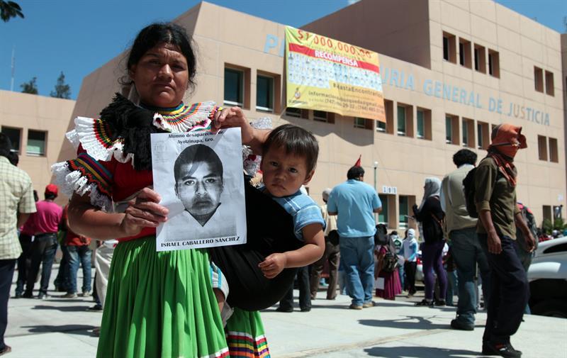 CHILPANCINGO (MÉXICO), 07/10/2014.- Una madre muestra la fotografía de su hijo, uno los 43 jóvenes desaparecidos durante la noche del 26 de septiembre tras un ataque perpetrado por policías municipales y miembros del grupo criminal Guerreros Unidos contra estudiantes de la Normal Rural de Ayotzinapa (escuela dedicada a la formación de maestros de primaria), hoy, martes 7 de octubre de 2014, a las afueras de la Procuraduría General de la República de la ciudad de Chilpancingo, capital del estado de Guerrero (México). Unos 110 miembros de la Policía del municipio mexicano de Iguala, donde desaparecieron 43 jóvenes, fueron enviados a un centro de entrenamiento para someterse a controles de confianza y saber si son aptos para ejercer o tienen algún tipo de vínculo con la delincuencia organizada. EFE/José Luis de la Cruz