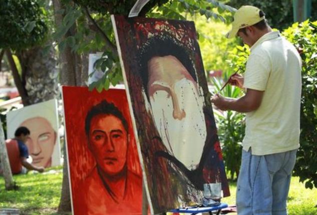 Artistas independientes, que apoyan a los 43 estudiantes desaparecidos, pintan el rostro de cada uno de los estudiantes en la plaza principal de Chilpancingo (México). 25 de octubre de 2014. (EFE/José Méndez).