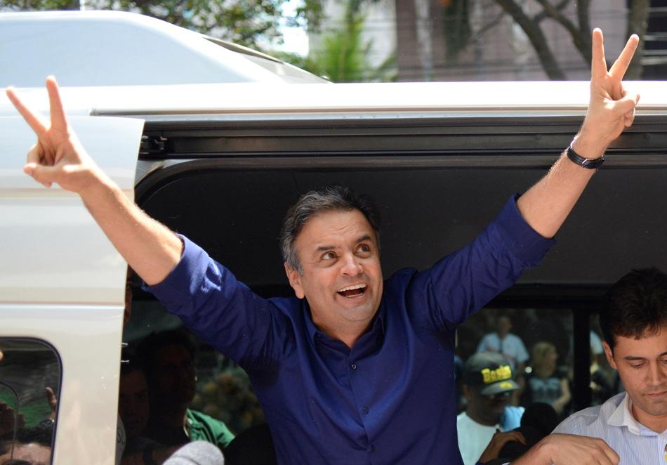 Aecio Neves, candidato presidencial del Partido de la Social Democracia Brasileña, hace el gesto de la victoria tras votar en Belo Horizonte, Brasil, el domingo 5 de octubre de 2014.  (AP foto/Eugenio Savio)