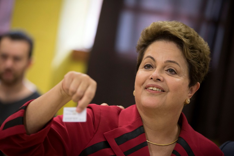 La presidenta de Brasil Dilma Rousseff, que busca su reelección por el Partido de los Trabajadores, muestra el comprobante que indica que ya emitió su voto electrónico en Porto Alegre, Brasil, el domingo 5 de octubre de 2014.  (AP foto/Felipe Dana)
