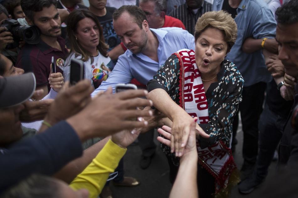 La presidenta Dilma Rousseff saluda a sus seguidores en la campaña por su reelección en una gira por Duque de Caxias en los suburbios de Rio de Janeiro, Brasil, el miércoles 22 de octubre de 2014. Rousseff debe enfrentar en segunda vuelta al opositor Aecio Neves el domingo 26 de octubrte de 2014. (AP Photo/Felipe Dana)