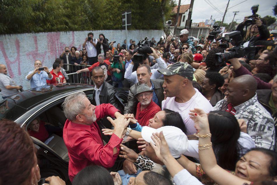 El expresidente brasileño Luiz Inácio Lula da Silva (i), saluda a seguidores del Partido de los Trabajadores tras votar hoy, domingo 5 de octubre de 2014, en un colegio electoral en la ciudad de Sao Bernardo do Campo (Brasil) en el marco de las elecciones en el país. EFE/Sebastião Moreira