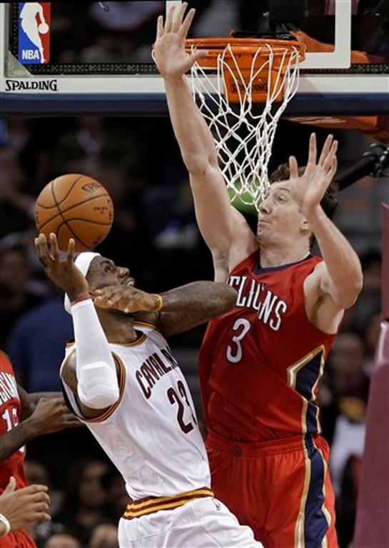 LeBron James, de los Cavaliers de Cleveland, recibe una falta del turco Omer Asik, de los Pelicans de New Orleans, en el partido del lunes 10 de noviembre de 2014 (AP Foto/Mark Duncan).