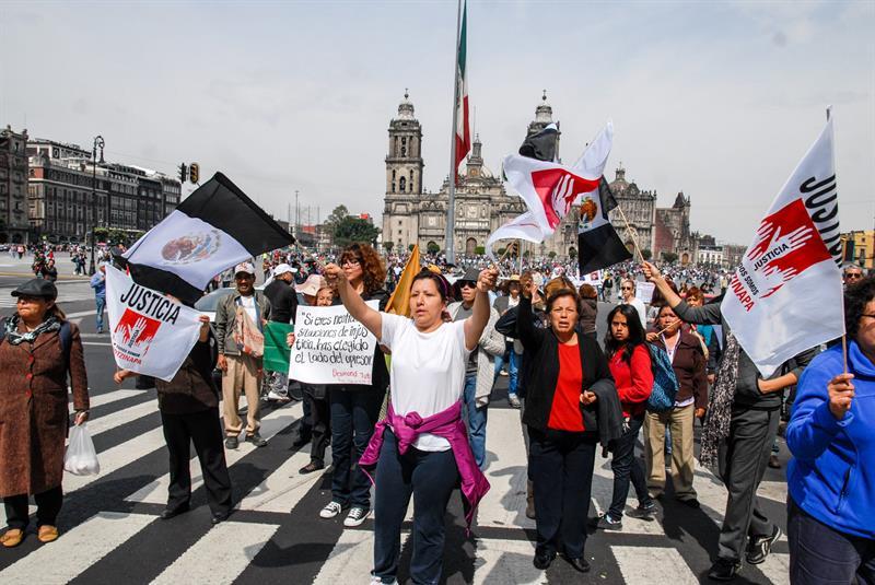 """CIUDAD DE MÉXICO (MÉXICO), 09/11/2014.- Manifestantes participan en la marcha """"43x43. Ni un desaparecido más"""" hoy, domingo 9 de noviembre de 2014, en Ciudad de México (México). Los participantes, que caminaron desde Iguala hasta la ciudad de México, arribaron al zócalo de Ciudad de México donde propusieron la creación de un movimiento nacional para dar voz al pueblo de México y poner fin a la ola de violencia existente en el país. A su llegada al Zócalo de la capital mexicana y tras una semana de caminata, los integrantes de este movimiento ofrecieron un mitin frente al Palacio Nacional en el que exigieron justicia por la desaparición de los 43 estudiantes en Iguala el 26 de septiembre.EFE/STR"""