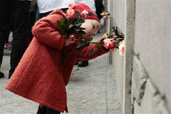 Hulda, de tres años, coloca flores en una grieta del antiguo muro de Berlín en memoria de las víctimas que murieron tratando de cruzar al Berlín Occidental, en la carre Bernauer de Berlín, Alemania, el 9 de noviembre de 2014. (AP Foto/Markus Schreiber)