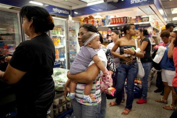Milagro Álvarez carga a su hija de cinco meses mientras hace fila en una sucursal de la tienda Farmatodo de Caracas, Venezuela, el viernes 24 de octubre de 2014. La tienda se niega a venderle más pañales debido a la política de racionamiento del gobierno que sólo le permite comprar dos paquetes de 20 pañales a la semana. (Foto de AP/Ariana Cubillos)
