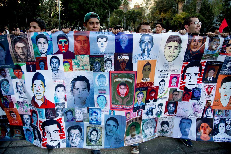 Manifestantes sostienen imágenes de los 43 estudiantes desaparecidos en el sureño estado mexicano de Guerrero, en la Ciudad de México el miércoles 5 de noviembre de 2014. (Foto AP/Eduardo Verdugo)