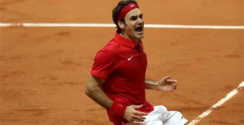 El suizo Roger Federer se arrodilla luego de vencer al francés Richard Gasquet en el primer juego de sencillos invertidos de la final de la Copa Davis en el estadio Pierre Mauroy de Lille, en el norte de Francia, el domingo 23 de noviembre de 2014. Suiza tomó ventaja de 3-1 para llevarse su primer título de Copa Davis. (Foto AP/Peter Dejong)