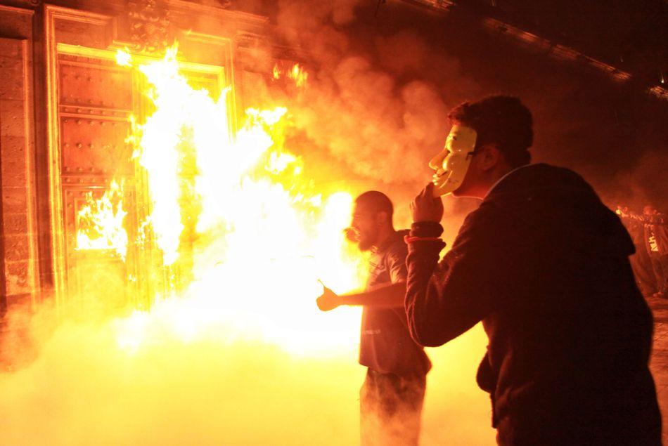 Una veintena de manifestantes escapuchados derribaron ayer las vallas de seguridad de los alrededores del Palacio Nacional, sede del Ejecutivo mexicano, y prendieron fuego a la puerta principal del histórico edificio. EFE/Sáshenka Gutiérrez