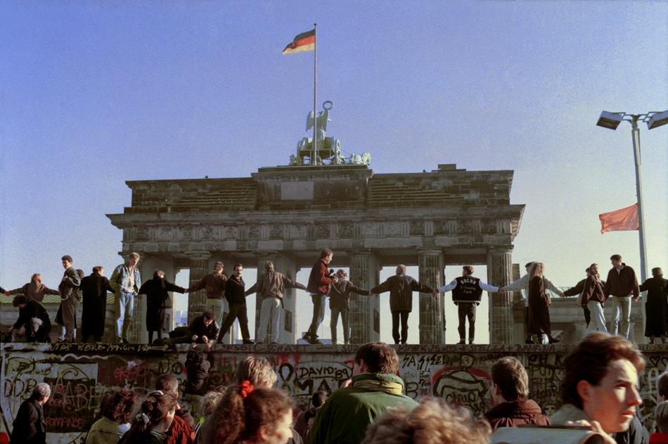 En esta imagen de archivo del 10 de noviembre de 1989, berlineses cantan y bailan sobre el Muro de Berlín para celebrar la apertura de las fronteras entre el este y el oeste de la ciudad. Miles de ciudadanos de la Alemania del Este se mudaron al Oeste después de que las autoridades abrieran los pasos de frontera a Occidente. (AP Foto/Thomas Kienzle)