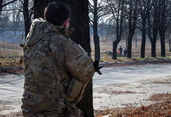 Un rebelde pro ruso monta guardia mientras dos mujeres caminan por una zona cerca de la línea del frente cerca del aeropuerto de Donetsk. (Foto AP/Dmitry Lovetsky)