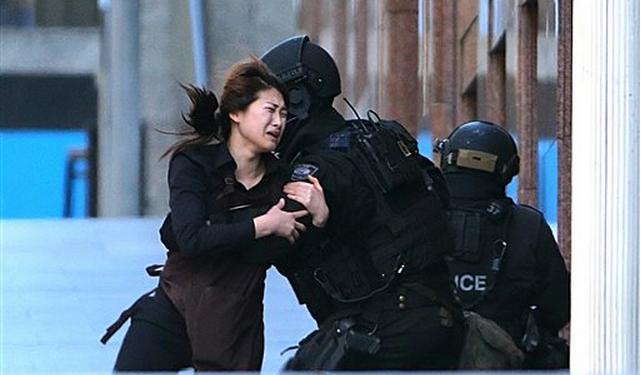 Una mujer corre para ponerse a salvo luego de salir de la cafetería Lindt en Sídney, Australia, donde permanecía secuestrada por un hombre armado (AP/Rob Griffith)