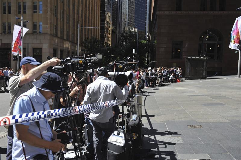 SÍDNEY (AUSTRALIA) 15/12/2014.- Medios de comunicación permanecen en las inmediaciones de la cafetería que un hombre armado tiene tomada desde primeras horas de la mañana en Sídney (Australia) hoy, lunes 15 de diciembre de 2014. Cinco personas han salido, por el momento, de la cafetería de Sídney que permanece tomada desde primeras horas de la mañana y donde hay un número indeterminado de rehenes. La Policía indicó que de momento no han logrado entablar conversaciones directamente con el secuestrador y se cree que el número de rehenes no supera los 30. EFE/Joel Carrett PROHIBIDO SU USO EN AUSTRALIA Y NUEVA ZELANDA