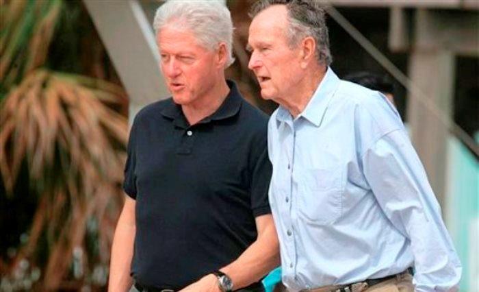 En esta fotografía de archivo del 14 de octubre de 2008, los ex presidentes Bill Clinton y George H.W. Bush caminan en la playa en Galveston, Texas. Bush permanecía hospitalizado en Houston el miércoles 24 de diciembre de 2014 tras experimentar dificultad para respirar, dijo un portavoz de la familia. (Foto AP/Pat Sullivan, archivo)
