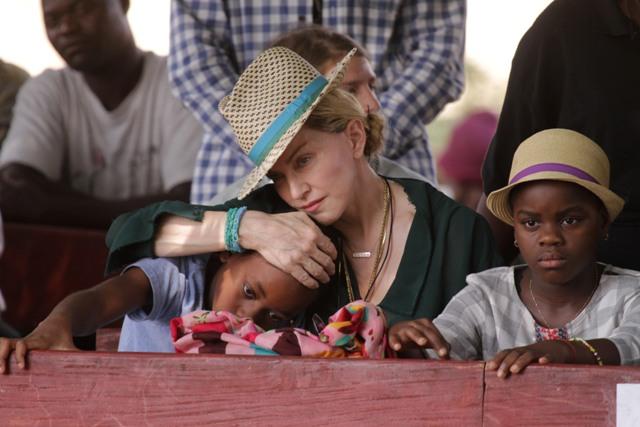 Madonna abraza a su hijo David, a la izquierda, junto a su hija Mercy, a la derecha, durante una visita a Kasungu, Malaui, el domingo 30 de noviembre del 2014. (AP Foto/Tsvangirayi Mukwazhi)