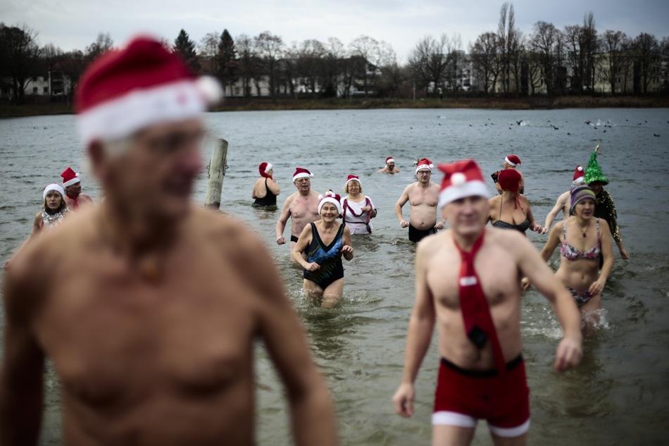 Miembros del club de nadadores invernales Seehunde Berlin (Focas Berlín), con gorras navideñas, realizan su chapuzón anual de Navidad en el lago Oranke de Berlín, jueves 25 de diciembre de 2014. (AP Foto/Markus Schreiber)