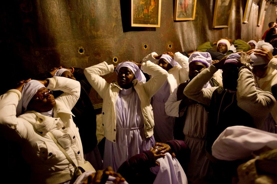 Peregrinos nigerianos rezan en la Gruta de la Iglesia de la Natividad, que se alza sobre el lugar donde tradicionalmente se cree que nació Jesús, Belén, Cisjordania, en la víspera de Navidad, miércoles 24 de diciembre de 2014. (AP Foto/Majdi Mohammed)