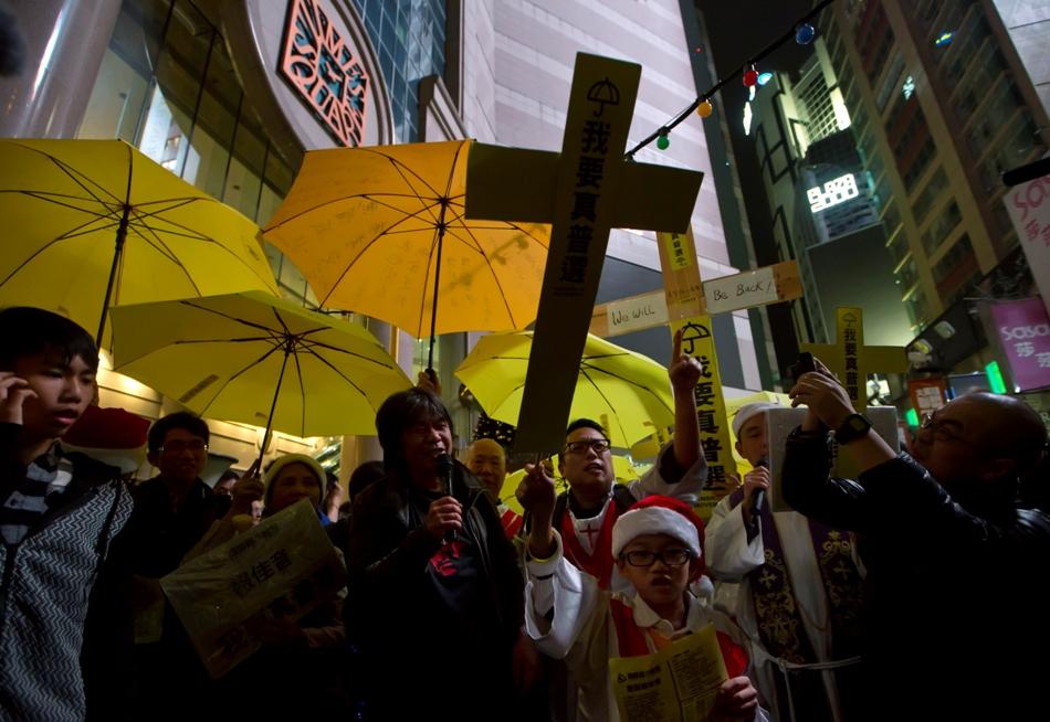 En la imagen, manifestantes pro democráticos sostienen paraguas amarillos y cruces de papel en las primeras horas del día de Navidad, en el distrito comercial Causeway Bay en Hong Kong, el 25 de diciembre de 2014, mientras piden un sufragio universal genuino. (AP Foto/Kin Cheung)