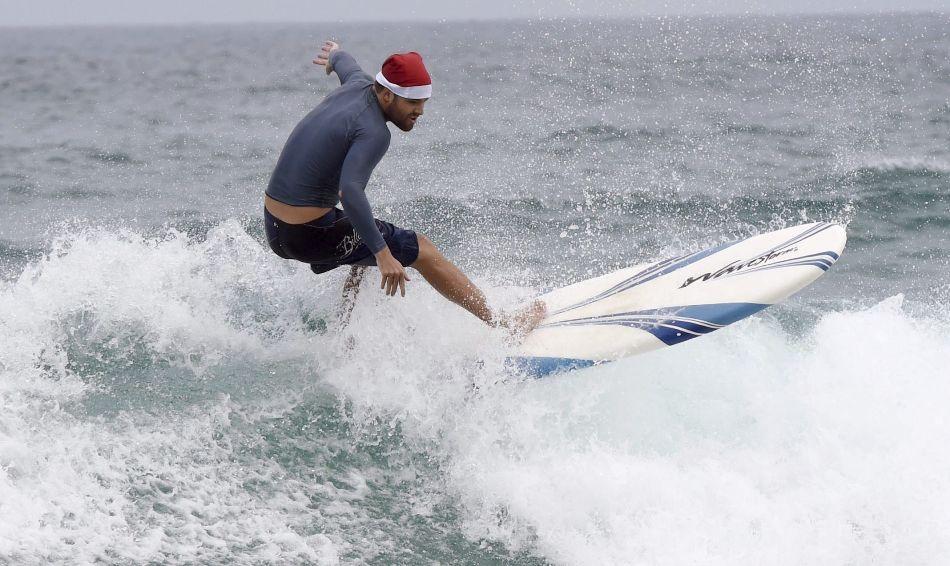 SÍDNEY (AUSTRALIA) 25/12/2014.- El surfista Guy Miller toma una ola con su tabla durante la tradicional celebración de Navidad en la playa de Bondi Beach de Sídney (Australia), hoy, 25 de diciembre de 2014. Familias y turistas se reúnen cada año en esta playa para conmemorar el día de Navidad, que coincide en pleno verano australiano. EFE/Dean Lewins