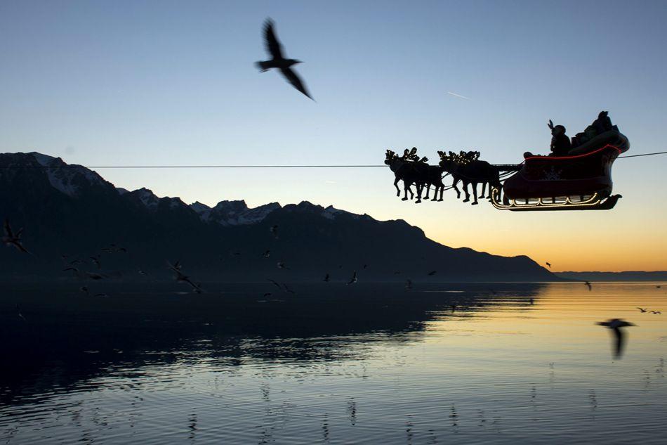 """MONTREUX (SUIZA), 23/12/2014.- Un hombre vestido de Papá Noel saluda desde su trineo volador conducido por renos desde el Lago de Ginebra frente a los Alpes franceses y suizos al atardecer durante la celebración de la vigésima edición del Mercado Navideño de Montreux, Suiza, hoy, martes 23 de diciembre de 2014. Papá Noel """"vuela"""" ayudado de un cable de 385 metros que cuelga sobre el mercado y el lago. EFE/Jean-Christophe Bott"""