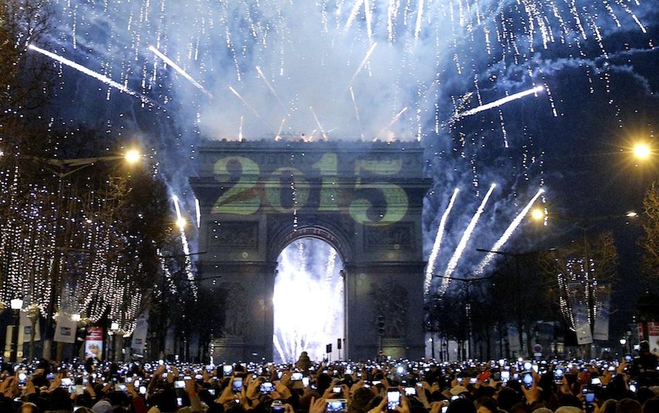 Asistentes a la fiesta de Año Nuevo toman fotografías de los fuegos artificiales para recibir 2015, en los Campos Elíseos, en París, el 1 de enero de 2015. (Foto AP/Christophe Ena)