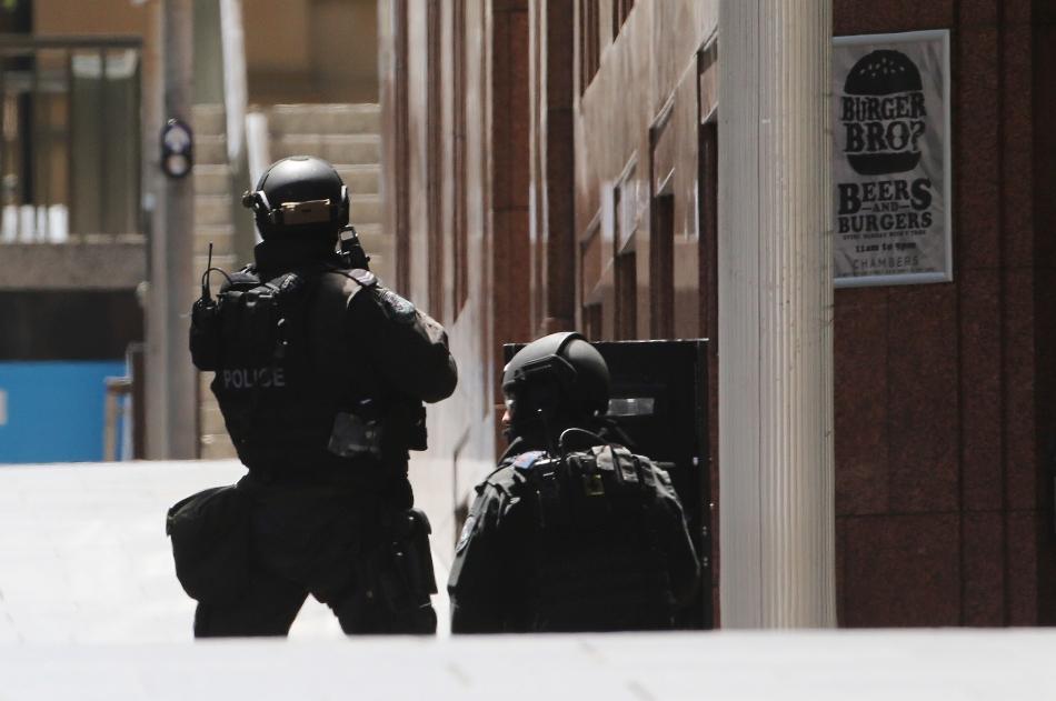 Policías junto a una cafetería donde se producía una crisis de rehenes en Sídney, Australia, el 15 de diciembre de 2014. (AP Foto/Rob Griffith)