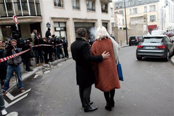 Varias personas frente al semanario satírico francés tras un ataque en París, el miércoles 7 de enero del 2015. Hombres enmascarados y fuertemente armados tomaron por asalto las oficinas del semanario el miércoles, con un saldo de por lo menos 12 muertos, antes de escapar, dijeron la policía y testigos. La publicación ha sido criticada con frecuencia por burlarse de los musulmanes. (Foto AP/Thibault Camus)