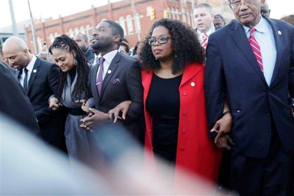 """La conductora de televisión Oprah Winfrey participa en una marcha con David Oyelowo (izquierda, quien interpretó a Martin Luther King Jr. en la película """"Selma""""), Ava DuVernay (izquierda, directora de """"Selma"""") y el rapero Common (a la extrema izquierda), hacia el puente Edmund Pettus en honor de Martin Luther King Jr., el domingo 18 de enero de 2015, en Selma, Alabama. (Foto AP/Brynn Anderson)"""
