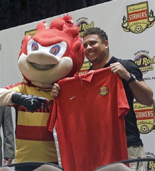 El brasileño Ronaldo posa con una camiseta y con la mascota de los Strikers de Fort Lauderdale, durante una conferencia de prensa realizada el miércoles 14 de enero de 2015 (AP Foto/Alan Díaz).