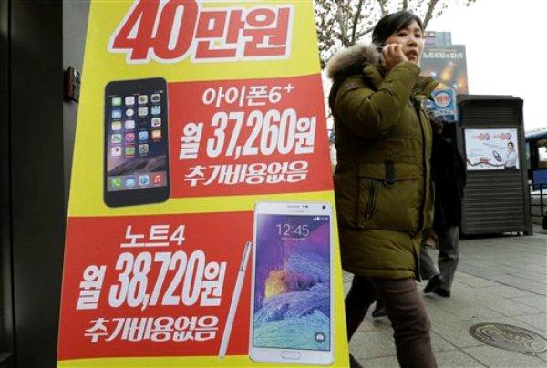 Un cartel publicitario muestra las imágenes de un iPhone 6 Plus de Apple (arriba) y un Galaxy NOTE 4 de Samsung Electronics fuera de una tienda de celulares en Seúl, Corea del Sur, el jueves 29 de enero de 2015. (Foto AP/Ahn Young-joon)