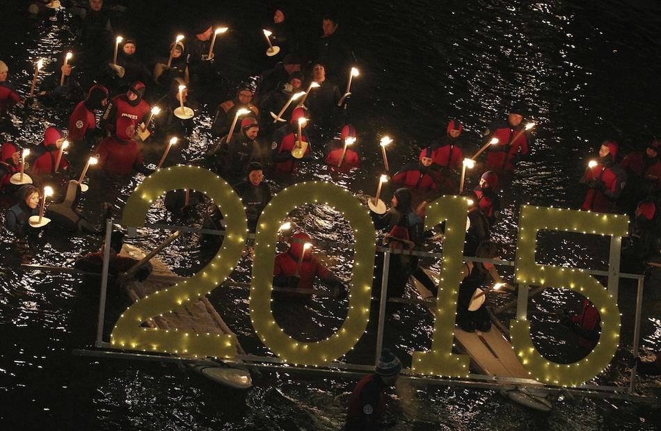 Decenas de personas participan en el tradicional baño con antorchas en las gélidas aguas del río Lech en Füssen, Baviera, Alemania, en el primer día de año nuevo, hoy, jueves 1 de enero de 2015. EFE/Karl-Josef Hildenbrand