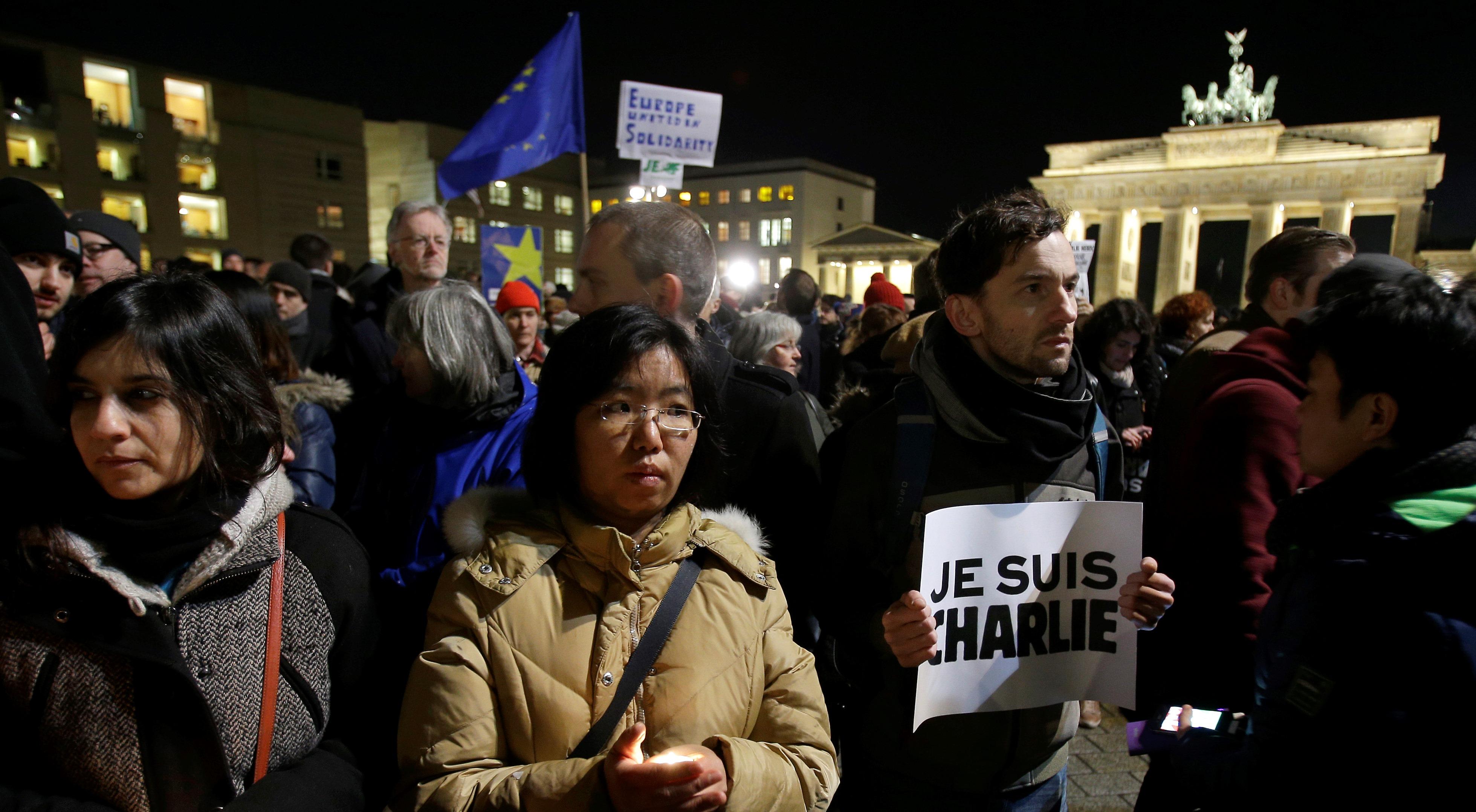 """Un hombre sostiene un cartel con el mensaje """"Yo soy Charlie"""" mientras participa en una manifestación frente a la Puerta de Brandemburgo en Berlín, Alemania, en protesta por el ataque al diario satírico francés Charlie Hebdo, el miércoles 7 de enero de 2015. (Foto AP/Michael Sohn)"""