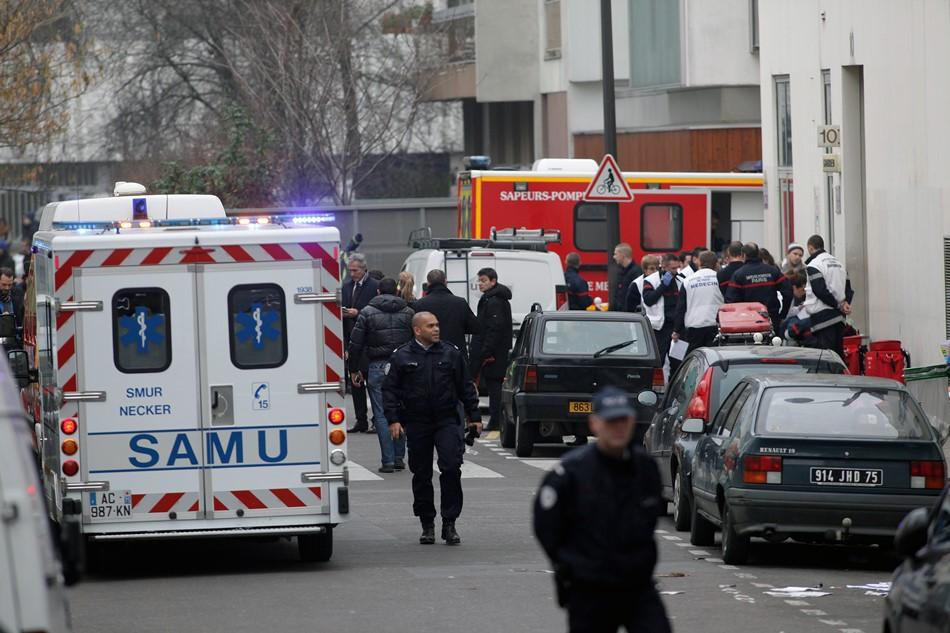 Agentes de policía y bomberos reunidos ante la sede del periódico satírico Charlie Hebdo en París, el 7 de enero de 2015. Once personas murieron en un ataque contra la sede del medio, según la policía. (AP Foto/Thibault Camus)