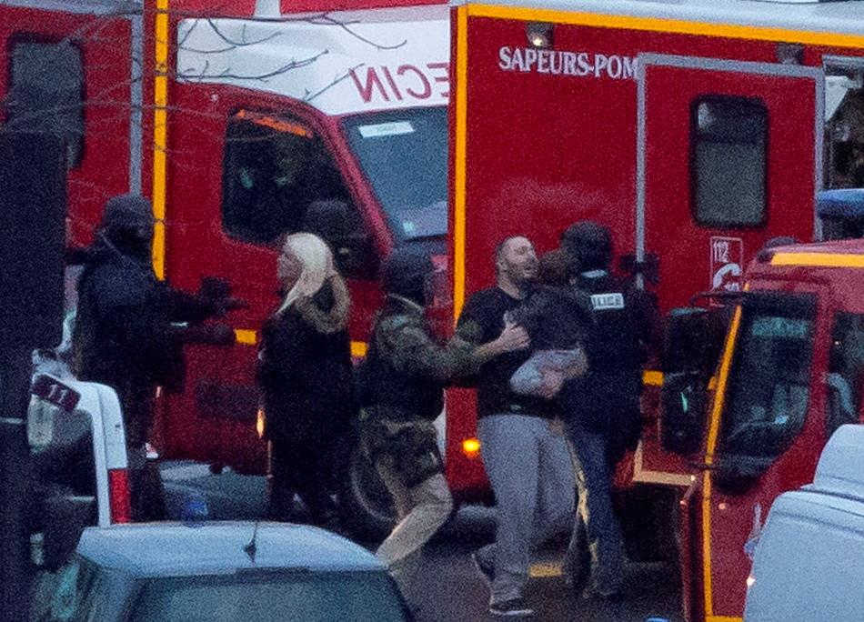 Un policía conduce a rehenes liberados después de un asalto policial en un mercado kosher en París, el viernes 9 de enero de 2015. (Foto AP/Michel Euler)