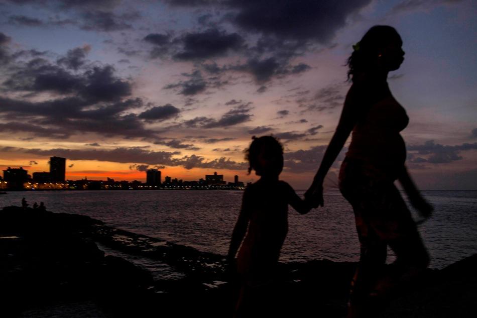 En esta foto del 3 de enero del 2015, una mujer lleva a una niña de la mano en el malecón de La Habana, Cuba. Para un extranjero, Cuba resulta un enigma. (AP Foto/Ramón Espinosa)
