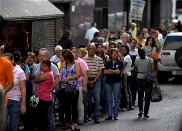Clientes forman fila en un supermercado en el centro de Caracas, Venezuela, el jueves 8 de enero de 2015. Tras los festejos del Año Nuevo los venezolanos volvieron una vez más a la cruda realidad de verse forzados a permanecer horas de filas para entrar a automercados en muchos casos en un frustrado intento de comprar los escasos productos básicos de consumo masivo. (AP Photo/Fernando Llano)