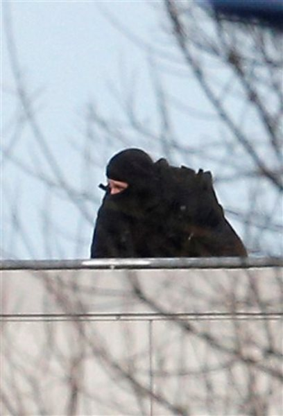 Un policía enmascarado en una azotea en Dammartin-en-Goele, al noreste de París,  donde fueron acorralados los dos hermanos sospechosos del ataque terrorista contra el semanario Charlie Hebdo el viernes 9 de enero de 2015. El viernes dos grupos de atacantes tomaron rehenes en la ciudad movilizando a cientos de fuerzas de seguridad en París. (Foto AP/Christophe Ena)