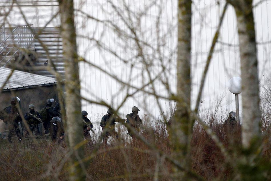 """Agentes del grupo especial de intervención de la policía, toman posiciones junto a una pequeña imprenta en una zona industrial de la localidad de Dammartin-en-Goele, al noreste de París (Francia), en la que permanecen atrincherados los hermanos Chérif y Said Kouachi, supuestos autores de los 12 asesinatos de la revista satírica """"Charlie Hebdo"""", hoy, viernes 9 de enero de 2015. La policía francesa se ha visto obligada a lanzar una segunda operación antiterrorista en París, después de que un individuo asaltara un supermercado y tomara varios rehenes, mientras trata de detener a los autores de la masacre de """"Charlie Hebdo"""". EFE/YOAN VALAT"""