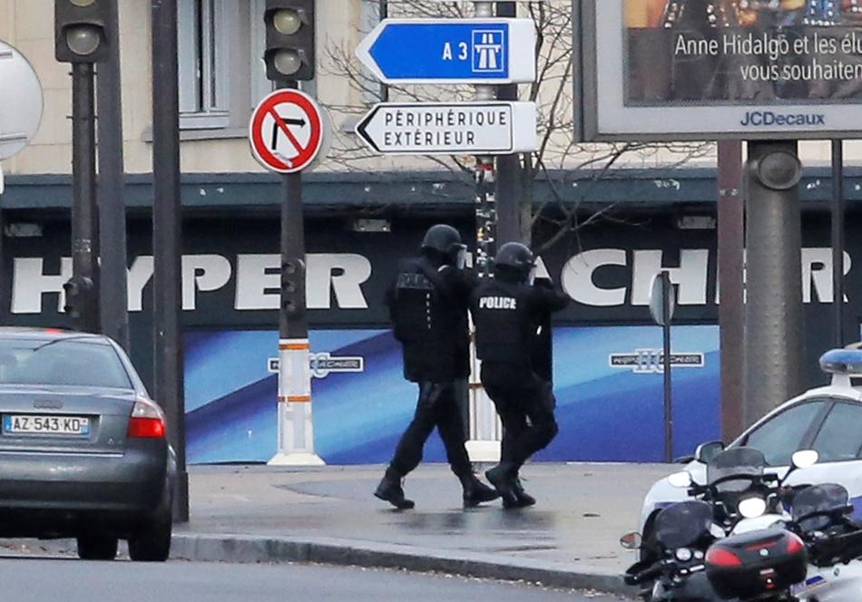 Un par de policías camina frente al mercado Hyper Cacher donde un hombre armado tenía como rehenes al menos a cinco personas, en París, el viernes 9 de enero de 2015. (Foto AP/Francois Mori)