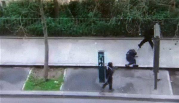 Unos hombres enmascarados pasan frente a un policía momentos después de dispararle fuera de las oficinas del semanario satírico Charlie Hebdo en París en una imagen tomada de un video amateur grabado el miércoles 7 de enero de 2015 por Jordi Mir. Resisdentes de París capturaron imágenes perturbadoras de dos hombres enmascarados disparándole en la cabeza a un policía tras el ataque en Charlie Hebdo. (Foto AP/Jordi Mir) NO SALES