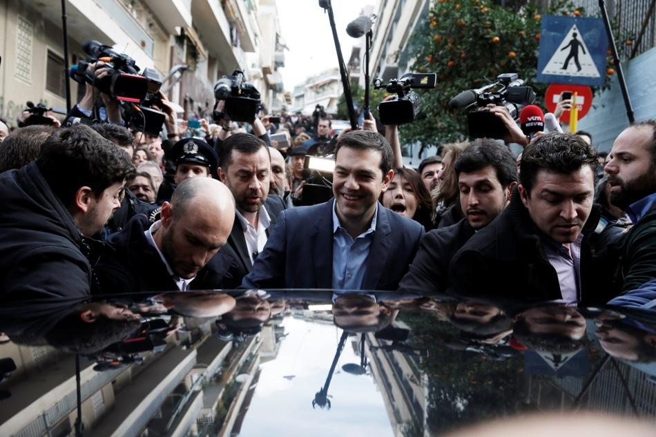 El líder del partido de la izquierda radical Syriza,Alexis Tsipras (centro), envuelto en una nube de medios de comunicación intenta llegar a su coche tras votar en Atenas, el 25 de enero de 2015. (Foto AP/Petros Giannakouris)