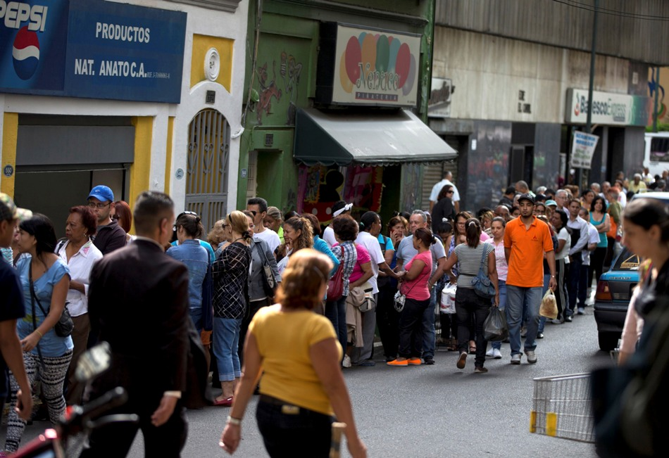 Clientes forman fila en un supermercado en el centro de Caracas, Venezuela, el jueves 8 de enero de 2015.  (AP Photo/Fernando Llano)