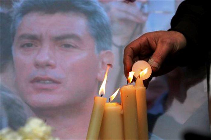 Personas encienden velas en memoria de Boris Nemtsov, al fondo, en el monumento a los presos políticos 'Piedra de Solovetsky' en San Petersburgo, Rusia, el sábado 28 de febrero de 2015. Nemtsov murió a tiros el sábado cerca del Kremlin, justo un día antes de una protesta planeada contra el gobierno. (Foto AP/Dmitry Lovetsky)
