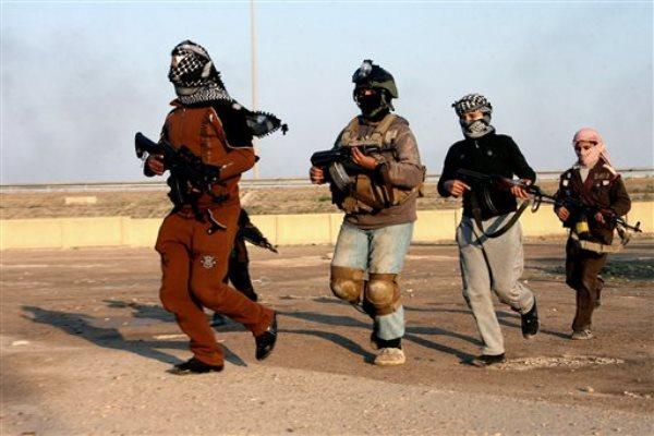 Cuatro individuos corren con sus rifles mientras patrullan Faluya el 5 de enero del 2014. La ciudad iraquí fue la primera que cayó en manos de extremistas suníes y es un buen ejemplo de la inoperancia de las fuerzas iraquíes para contener una ofensiva de la organización Estado Islámico. Irán está llenando ese vacío y es el principal responsable de que EI no haya llegado a Bagdad. (AP Photo, File)