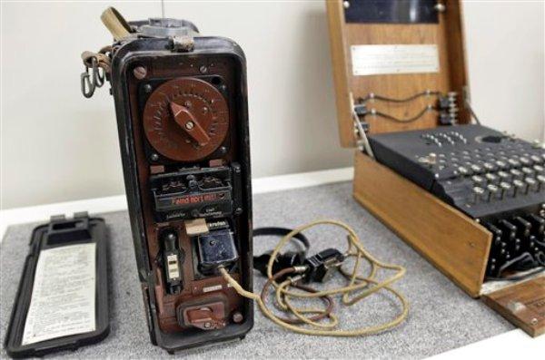 """Un radio de infantería nazi con la advertencia """"¡el enemigo está escuchando!"""", junto a una máquina codificadora nazi Enigma en exhibición en el Museo de la Segunda Guerra Mundial en Natick, Massachusetts, el miércoles 18 de febrero de 2015.  (Foto AP/Elise Amendola)"""